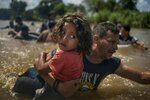 In this Oct. 29, 2018, photo taken by Reuters photographer Adrees Latif, Luis Acosta carries 5-year-old Angel Jesus, both from Honduras, as a caravan of migrants from Central America en route to the United States crossed through the Suchiate River into Mexico from Guatemala in the outskirts of Tapachula. A team of Reuters photographers won the Pulitzer Prize in breaking news photography for their coverage of migrants as they journeyed to the U.S. from Central and South America. (Adrees Latif/Reuters/The Pulitzer Prizes via AP)