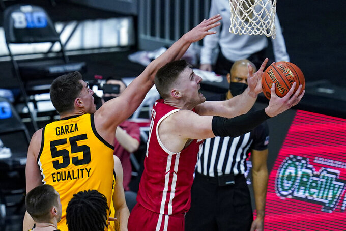 Wisconsin forward Micah Potter (11) shoots next to Iowa center Luka Garza (55) during the second half of an NCAA college basketball game at the Big Ten Conference men's tournament in Indianapolis, Friday, March 12, 2021. (AP Photo/Michael Conroy)