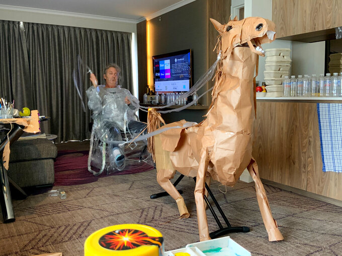 CORRECTS NAME - David Marriott poses with his paper horse Russel in his hotel room in Brisbane, Australia, April 6, 2021. While in quarantine inside his Brisbane hotel room, the art director was bored and started making a cowboy outfit from the paper bags his meals were being delivered in. His project expanded to include a horse and a clingfilm villain that he has daily adventures with, in images that have gained a huge online following. (David Marriott via AP)