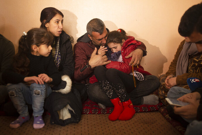 In this Feb. 12, 2020 photo, Malak Saad Dakhel, an 11 year-old Yazidi, is overwhelmed by journalists and well-wishers as her family tries to comfort her after her escape from Syria, in Sharia, Iraq. She was captured by Islamic State militants in 2014 and was recently found at al-Hol camp living with a Syrian family. (AP Photo/Maya Alleruzzo)