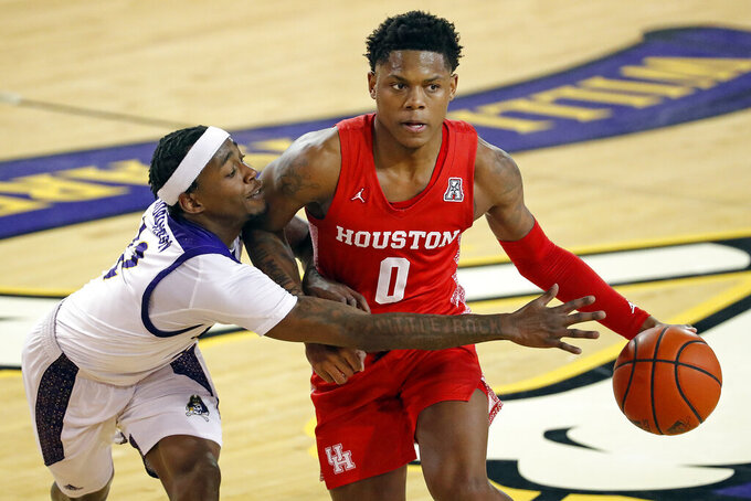 Houston's Marcus Sasser (0) looks to pass the ball as he is challenged by East Carolina's Tremont Robinson-White (12) during the first half of an NCAA college basketball game in Greenville, N.C., Wednesday, Feb. 3, 2021. (AP Photo/Karl B DeBlaker)