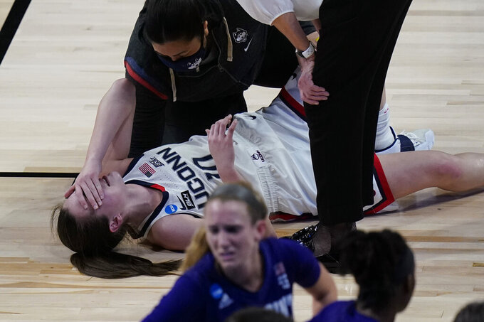 UConn guard Nika Muhl (10) reacts after she was injured during the first half of a college basketball game against High Point in the first round of the women's NCAA tournament at the Alamodome in San Antonio, Sunday, March 21, 2021. (AP Photo/Eric Gay)