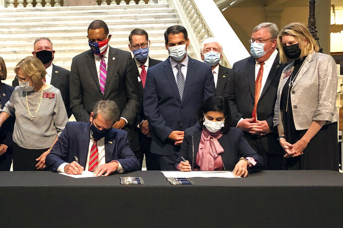 Georgia Gov. Brian Kemp, left, and Centers for Medicare and Medicaid Services Administrator Seema Verma sign health care waivers at the state Capitol in Atlanta, Thursday, Oct. 15, 2020. Georgia's plans would provide Medicaid access to adults who make less than poverty level incomes who meet work requirements, and leave private brokers as the only avenue to buy federally-subsidized private insurance for people with above-poverty incomes. (AP Photo/Jeff Amy)