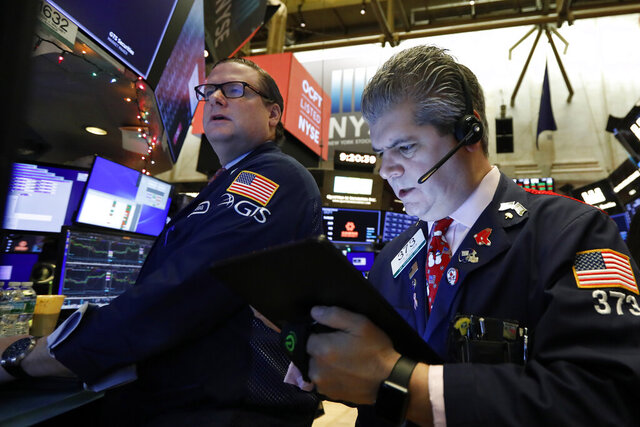 Specialist Gregg Maloney, left, and trader John Panin work on the floor of the New York Stock Exchange, Friday, Dec. 13, 2019. After months of waiting, markets had a muted reaction to news Friday that the US and China had reached an initial deal on trade. (AP Photo/Richard Drew)