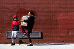 A woman carries a box of donated food and educational materials that she picked up at John H. Webster Elementary School in Philadelphia, Thursday, March 26, 2020. Gov. Tom Wolf's administration reported more new coronavirus-related deaths in Pennsylvania on Wednesday. Residents are ordered to stay home, with few exceptions. (AP Photo/Matt Rourke)