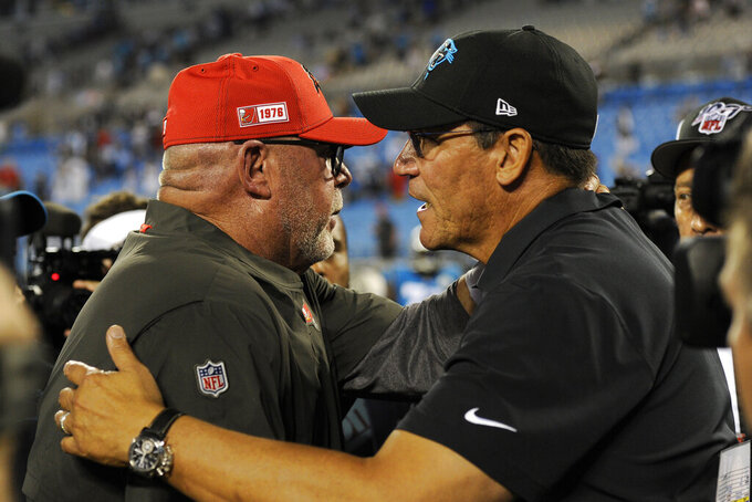 Tampa Bay Buccaneers head coach Bruce Arians, left, and Carolina Panthers head coach Ron Rivera speak following an NFL football game in Charlotte, N.C., Friday, Sept. 13, 2019. (AP Photo/Mike McCarn)
