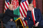 FILE - In this Thursday, Nov. 28, 2019 file photo, President Donald Trump shakes hands during a meeting with Afghan President Ashraf Ghani during a surprise Thanksgiving Day visit, at Bagram Air Field, Afghanistan. A new survey released by the Asia Foundation Tuesday, Dec. 3, 2019, says Afghans are increasingly fearful for their personal safety, but slightly more believe their war-weary country is moving in the right direction compared to previous years. (AP Photo/Alex Brandon, File)