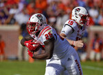North Carolina State's Reggie Gallaspy Jr. takes the hand off from Ryan Finley during the first half of an NCAA college football game against Clemson, Saturday, Oct. 20, 2018, in Clemson, S.C. (AP Photo/Richard Shiro)