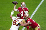 San Francisco 49ers quarterback Nick Mullens (4) throws under pressure from Washington Football Team defensive end Ryan Kerrigan (91) during the first half of an NFL football game, Sunday, Dec. 13, 2020, in Glendale, Ariz. (AP Photo/Ross D. Franklin)