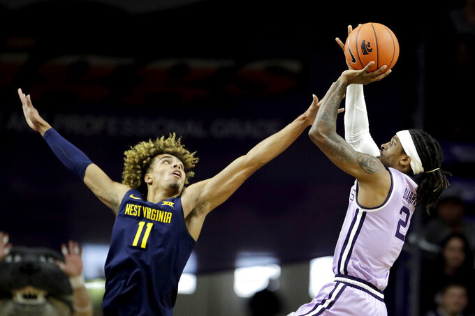 Kansas State's Cartier Diarra (2) shoots over West Virginia's Emmitt Matthews Jr. (11) during the first half of an NCAA college basketball game Saturday, Jan. 18, 2020, in Lawrence, Kan. (AP Photo/Charlie Riedel)