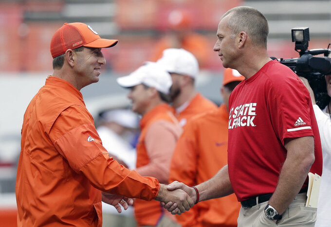 FILE - In this Nov. 4, 2017, file photo, Clemson head coach Dabo Swinney, left, and North Carolina State head coach Dave Doeren shake hands prior to an NCAA college football game in Raleigh, N.C. Clemson and North Carolina State play on Saturday, Oct. 20.  (AP Photo/Gerry Broome, File)