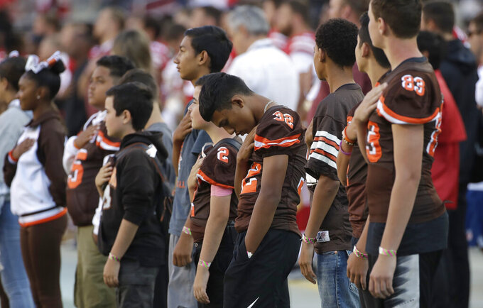 Gilroy (Calif.) Pop Warner football players observe a moment of silence for victims of shootings in Gilroy; El Paso, Texas; and Dayton, Ohio, before an NFL preseason football game between the San Francisco 49ers and the Dallas Cowboys in Santa Clara, Calif., Saturday, Aug. 10, 2019. (AP Photo/Jeff Chiu)