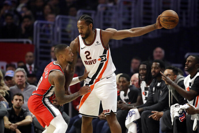 Portland Trail Blazers' Damian Lillard, left, defends on Los Angeles Clippers' Kawhi Leonard (2) during the first half of an NBA basketball game Tuesday, Dec. 3, 2019, in Los Angeles. (AP Photo/Marcio Jose Sanchez)