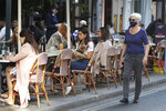 A woman wears a mask as she passes people dinning out in London, Monday, Sept. 21, 2020. Britain's top medical advisers have painted a grim picture of exponential growth in illness and death if nothing is done to control the second wave of coronavirus infections, laying the groundwork for the government to announce new restrictions later this week. (AP Photo/Kirsty Wigglesworth)