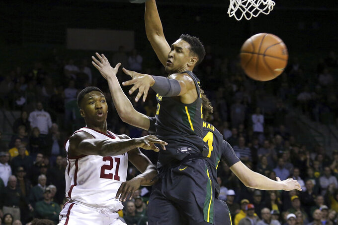 Oklahoma forward Kristian Doolittle (21) passes the ball past Baylor forward Tristan Clark (25) in the first half of an NCAA college basketball game Monday, Jan. 20, 2020, in Waco, Texas. (AP Photo/ Jerry Larson)