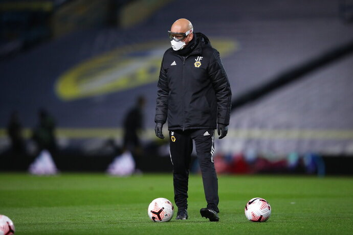 A Leeds United's assistant coach, name not available, wearing protective goggles and a mask, to help prevent the spread of coronavirus, helps players to warm up prior to the English Premier League soccer match between Leeds United and Wolverhampton Wanderers at Elland Road ground in Leeds, England, Monday, Oct. 19, 2020. (Martin Rickett/Pool via AP)