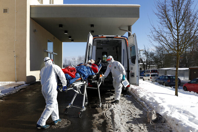 Medical workers move a covid-19 patient into an ambulance at a hospital overrun by the covid pandemic in Cheb, Czech Republic, Friday, Feb. 12, 2021. The Czech government has imposed a complete lockdown of the three hardest-hit counties to help contain the spread of a highly contagious variant of the coronavirus. The meeasures will became effective Friday for the two counties in western Czech Republic on the German border Cheb and Sokolov and another county in the northern part of the country Trutnov located on the border with Poland. (AP Photo/Petr David Josek)