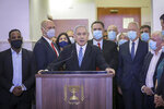 POOL - In this Sunday, May 24, 2020 photo, Israeli Prime Minister Benjamin Netanyahu accompanied by members of his Likud Party in masks delivers a statement before entering the district court in Jerusalem. Benjamin Netanyahu's fulminating tirade against Israel's legal system on the steps of a Jerusalem courthouse managed to even overshadow the opening of his historic corruption trial. Surrounded by loyal deputies, and with hundreds of impassioned supporters cheering him outside and echoing his charges, Netanyahu's onslaught capped a years-long campaign that has bitterly divided the country and raised fears of irreparably tearing apart the delicate fabric of Israeli society. (AP Photo/Yonatan Sindel/Pool Photo via AP)