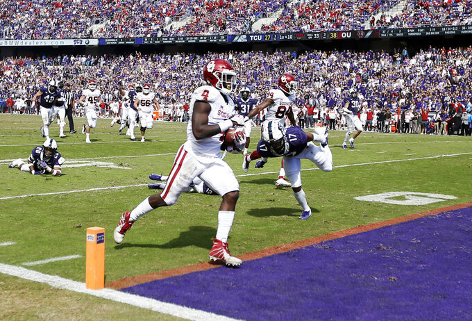 Oklahoma running back Trey Sermon (4) scores a touchdown during the second half of an NCAA college football game against TCU, Saturday, Oct. 20, 2018, in Fort Worth, Texas. Oklahoma won 52-27. (AP Photo/Brandon Wade)