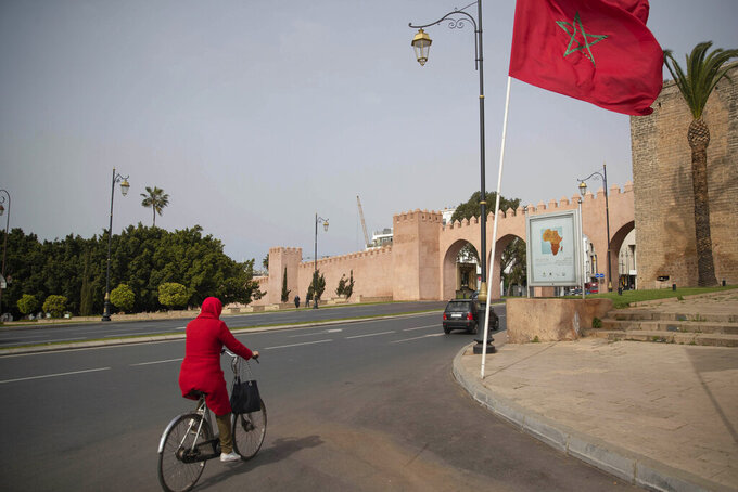 A woman cycles along a virtually empty avenue, on the day Moroccan authorities called on citizens to limit their movements and comply with self isolation regulations, in downtown Rabat, Morocco, Wednesday, March 18, 2020. For most people, the new coronavirus causes only mild or moderate symptoms, such as fever and cough. For some, especially older adults and people with existing health problems, it can cause more severe illness, including pneumonia. (AP Photo/Mosa'ab Elshamy)