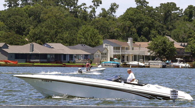 FILE - Pleasure boats cut through the waters of Lake Conroe, near Conroe, Texas on June 10, 2014. Travelers are leaning toward less-crowded vacation destinations this year. (AP Photo/Pat Sullivan, File)
