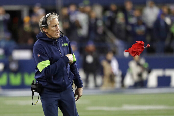 Seattle Seahawks head coach Pete Carroll throws a challenge flag near the end of an NFL football game against the Arizona Cardinals, Sunday, Dec. 22, 2019, in Seattle. (AP Photo/Elaine Thompson)