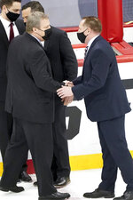 Minnesota Duluth coach Scott Alan Sandelin, left, greets Massachusetts coach Greg Carvel after an NCAA men's Frozen Four hockey semifinal in Pittsburgh, early Friday, April 9, 2021. Massachusetts won 3-2 and will face St. Cloud State in the championship game Saturday. (AP Photo/Keith Srakocic)