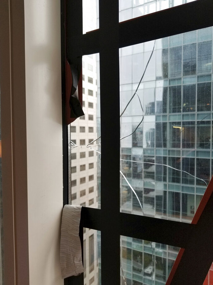 This recent but undated photo provided by the San Francisco Department of Building Inspection shows a window that has cracked in the Millennium Tower Building in San Francisco. City officials are demanding that managers of the sinking condominium building where a window recently cracked comply with several safety measures needed to keep the public safe. Department of Building Inspection Assistant Director Ronald Tom said Thursday, Sept. 13, 2018 that Millennium Tower management has to repair a window washing crane, inspect all units and install a canopy around the entire perimeter of the 58-story building by Friday afternoon. (Department of Building Inspection via AP)