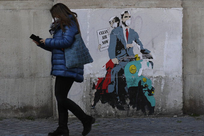 """A woman walks past a poster depicting a scene from the famed movie """" Roman Holiday"""" with Gregory Peck and Audrey Hepburn wearing surgical masks as riding a Lambretta scooter in Rome, Friday, April 9, 2021. Italy has seen a stabilizing of the new variant-fueled infections over the past three weeks, though its daily death count remains stubbornly high, averaging between 300-500 COVID-19 victims per day, and its ICU capacity for virus patients is well over the threshold set by the government. (AP Photo/Gregorio Borgia)"""