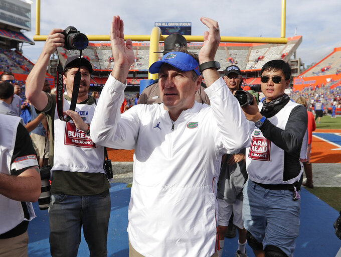 Florida head coach Dan Mullen, center, applauds fans as he leaves the field after defeating South Carolina in an NCAA college football game, Saturday, Nov. 10, 2018, in Gainesville, Fla. (AP Photo/John Raoux)