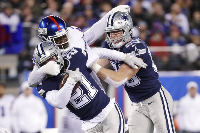 New York Giants linebacker Markus Golden (44) tackles Dallas Cowboys running back Ezekiel Elliott (21) during the first quarter of an NFL football game, Monday, Nov. 4, 2019, in East Rutherford, N.J. (AP Photo/Adam Hunger)