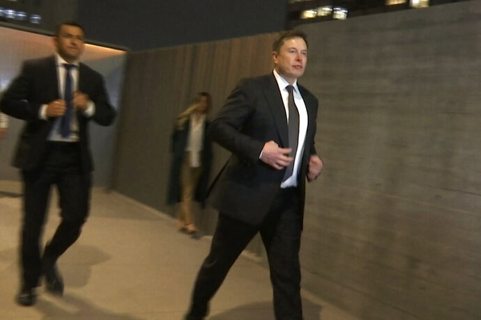 In this frame grab from video, Tesla CEO Elon Musk leaves court, Tuesday, Dec. 3, 2019, in Los Angeles. Musk denied that he meant to call a British cave diver a pedophile when he dubbed him