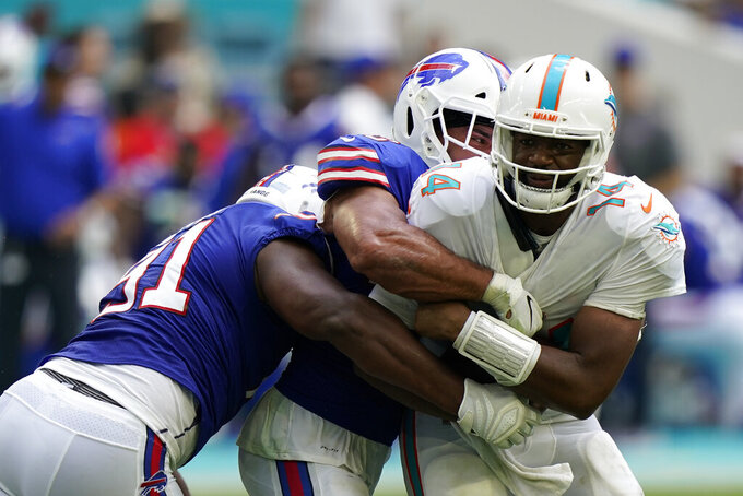 Miami Dolphins quarterback Jacoby Brissett (14) is sacked by Buffalo Bills outside linebacker Matt Milano (58), back, and Buffalo Bills defensive tackle Ed Oliver (91), second left, during the first half of an NFL football game, Sunday, Sept. 19, 2021, in Miami Gardens, Fla. (AP Photo/Wilfredo Lee)