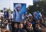 Protesters chant anti US slogans and carry posters with pictures of Qais al-Khazali and Arabic that reads