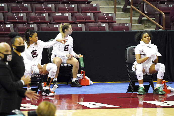 South Carolina guard Zia Cooke, right, Olivia Thompson, and LeLe Grissett, remain seated during the conclusion of the national anthem, as coaches Dawn Staley and Fred Chmiel, left, stand on the sideline before an NCAA college basketball game against Charleston Wednesday, Nov. 25, 2020, in Columbia, S.C. South Carolina won 119-38. (AP Photo/Sean Rayford)