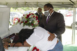Funeral director Shawn Troy comforts a distraught mourner during a graveside service at Hillcrest Cemetery outside Mullins, S.C., on Monday, May 24, 2021. His father, William Penn Troy Sr., died of COVID-19 in August 2020, one of many Black funeral directors to succumb during the pandemic. (AP Photo/Allen G. Breed)