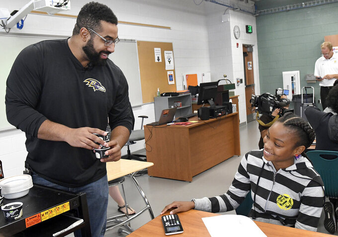 FILE - Baltimore Ravens lineman and math scholar John Urschel, left, hands out ice cream to Chelsy Valerio, 14, of Baltimore, during a lesson at Dundalk High School during the launch of Texas Instruments' STEM Behind Cool Careers series in Baltimore, in this Tuesday, July 18, 2017, file photo. John Urschel has found that a master's degree in mathematics, his stature as an accomplished author and his pending PhD at MIT isn't necessarily enough to sell young students on the benefit of crunching numbers. What really makes him interesting to most kids is that he's a former NFL player who opted to immerse himself in math. (Steve Ruark/AP Images for Texas Instruments, File)