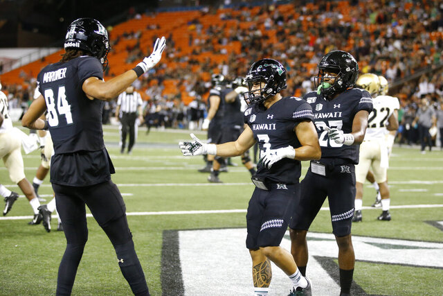 Hawaii wide receiver Jason-Matthew Sharsh, center, celebrates with teammates after he scored a touchdown against Army during the first half of an NCAA college football game Saturday, Nov. 30, 2019 in Honolulu. (AP Photo/Marco Garcia)