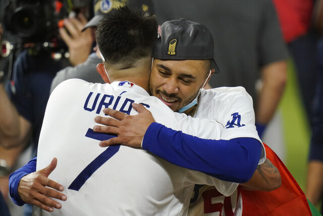 Los Angeles Dodgers pitcher Julio Urias and Mookie Betts celebrate after defeating the Tampa Bay Rays 3-1 to win the baseball World Series in Game 6 Tuesday, Oct. 27, 2020, in Arlington, Texas. (AP Photo/Eric Gay)