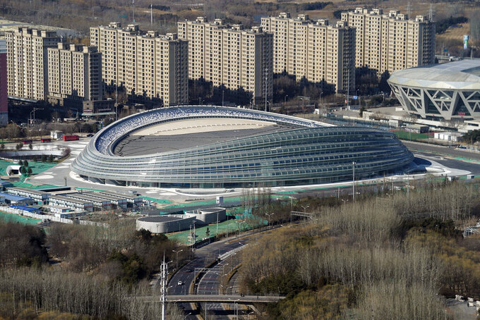 """Vehicles move past the new completed National Speed Skating Oval near the Olympics park in Beijing Tuesday, Feb. 2, 2021. The 2022 Beijing Winter Olympics will open a year from now. Most of the venues have been completed as the Chinese capital becomes the first city to hold both the Winter and Summer Olympics. Beijing held the 2008 Summer Olympics. But these Olympics are presenting some major problems. They are already scarred by accusations of rights abuses including """"genocide""""against more than 1 million Uighurs and other Muslim ethnic groups in western China. (AP Photo/Andy Wong)"""
