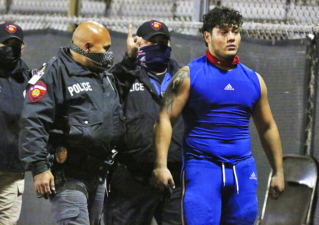 Edinburg's Emmanuel Duron is escorted out of the stadium by police after charging a referee during a high school football zone play-in game against Pharr-San Juan-Alamo on Thursday, Dec. 3, 2020, in Edinburg, Texas. (Joel Martinez/The Monitor via AP)