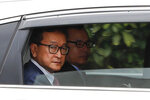 Cambodia's exiled opposition leader Sam Rainsy looks out from a car as he arrive at Parliament House in Kuala Lumpur, Tuesday, Nov. 12, 2019. Sam Rainsy landed in Kuala Lumpur in a bid to return to his homeland after Thailand had earlier blocked him from entering. (AP Photo/Vincent Thian)