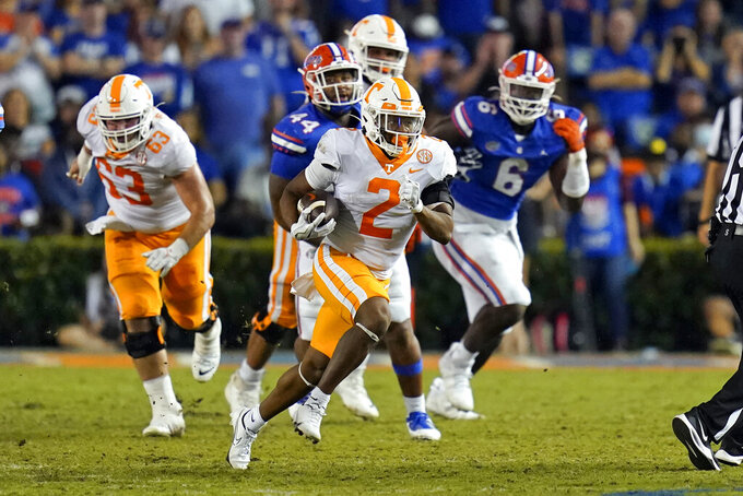 Tennessee running back Jabari Small (2) gets past Florida defensive lineman Daquan Newkirk (44) and defensive lineman Zachary Carter (6) for a gain during the first half of an NCAA college football game, Saturday, Sept. 25, 2021, in Gainesville, Fla. (AP Photo/John Raoux)