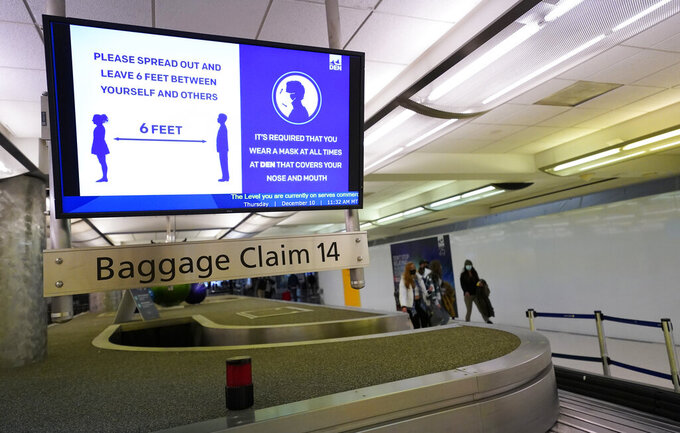 FILE - In this Dec. 10, 2020, file photo, an electronic sign warns travelers to maintain social distance in the terminal of Denver International Airport in Denver. About one-fifth of flight attendants say they've gotten into a physical incident with a passenger this year. That's according to a survey by their union. The Association of Flight Attendants says it wants people who act up during flights to face criminal prosecution — not just fines. Airlines have reported more than 3,600 cases of unruly passengers this year. Disputes over face masks are the most common trigger. Federal rules require face masks on planes until mid-Sept (AP Photo/David Zalubowski, File)