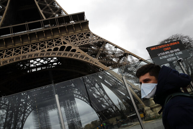 A man wearing a mask walks pasts the Eiffel tower closed after the French government banned all gatherings of over 100 people to limit the spread of the virus COVID-19, in Paris, Saturday, March 14, 2020. For most people, the new coronavirus causes only mild or moderate symptoms. For some it can cause more severe illness, especially in older adults and people with existing health problems. (AP Photo/Christophe Ena)