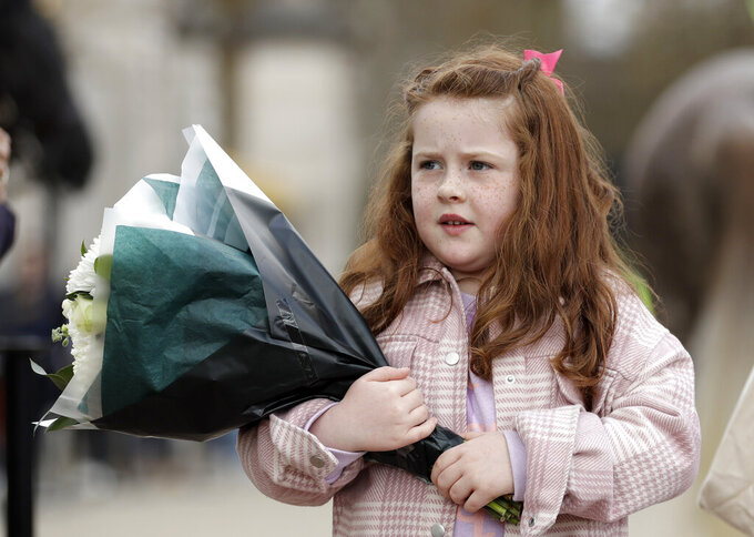 A young girl prepares to leave flowers in front of the gate at Buckingham Palace in London, after the announcement of the death of Britain's Prince Philip, Friday, April 9, 2021. Buckingham Palace officials say Prince Philip, the husband of Queen Elizabeth II, has died. He was 99. Philip spent a month in hospital earlier this year before being released on March 16 to return to Windsor Castle. (AP Photo/Matt Dunham)