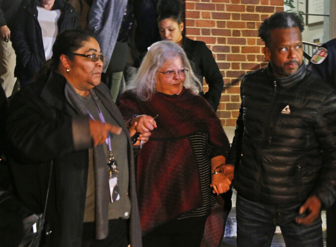 "Susan Bro, center, mother of Heather Heyer, is escorted down the steps of the courthouse after a guilty verdict was reached in the trial of James Alex Fields Jr., Friday, Dec. 7, 2018, at Charlottesville General district court in Charlottesville, Va. Fields was convicted of first degree murder in the death of Heather Heyer as well as nine other counts during a ""Unite the Right"" rally in Charlottesville . (AP Photo/Steve Helber)"