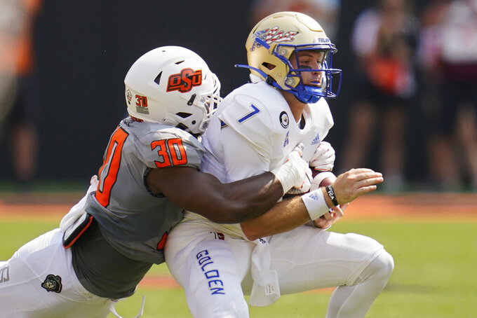 Tulsa quarterback Davis Brin (7) is tackled by Oklahoma State defensive end Collin Oliver (30) in the first half of an NCAA college football game, Saturday, Sept. 11, 2021, in Stillwater, Okla. (AP Photo/Sue Ogrocki)