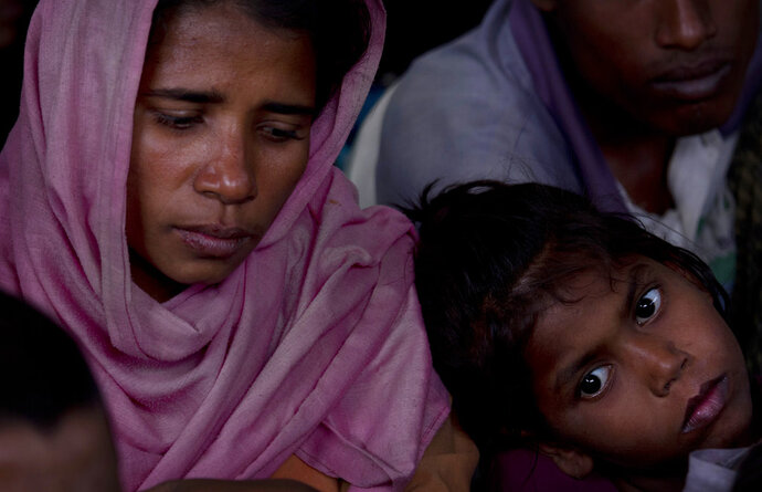 A newly arrived Rohingya family waits at a temporary shelter before their registration at Nayapara refugee camp, some 69 kilometres (43 miles) from in Cox bazar, Bangladesh, Saturday, Jan. 13, 2018. In Rakhine state of Myanmar, government troops have been accused of