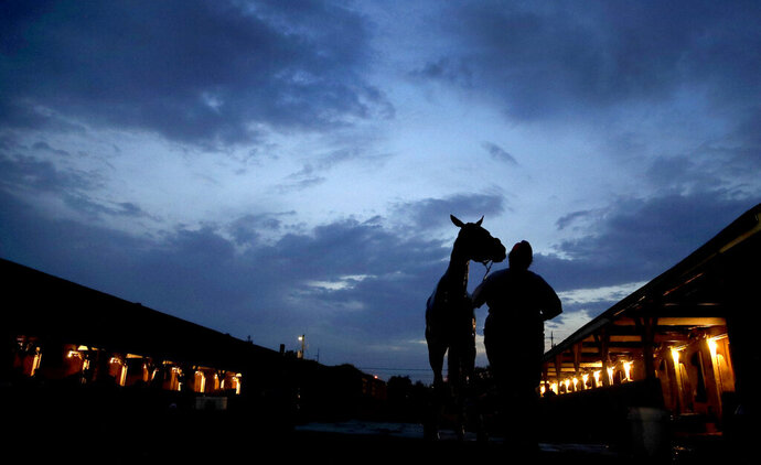 A horse gets a bath after an early-morning workout at Churchill Downs Tuesday, April 30, 2019, in Louisville, Ky. (AP Photo/Charlie Riedel, File)